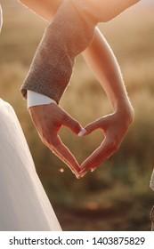 Schöne Hand Herz Symbol Form der Liebe Nahaufnahme Bild. Original Idee der Hochzeitsfamilie Makrofoto des Glücks. Happy-Männchen und Weibliche Hände Naturhintergrund Sonnenlichter Außenkonzept