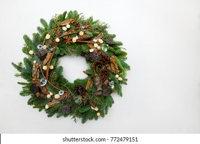 Beautiful hand made Christmas wreath isolated on white background, green spruce branches decorated with pine cones and other decorations