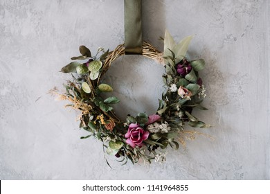 Beautiful hand made everlasting dry wreath made of roses, wheat and eucalyptus on the grey wall background