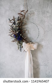 Beautiful hand made everlasting dry wreath made of dry flowers, eucalyptus tied with tender pastel coloured bow on the grey wall background