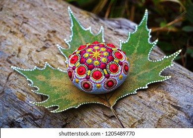 Beautiful hand painted mandala rock lying on a maple leaf