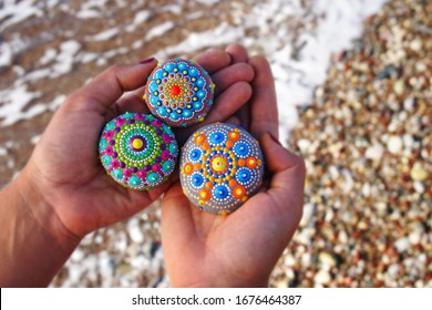 Beautiful hand painted mandala rock hold in hands