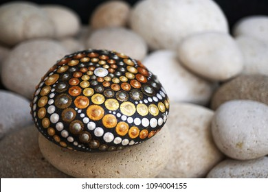 Beautiful hand painted mandala stone lies on the rocks