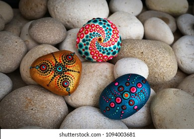 Beautiful hand painted mandala stones lies on the rocks