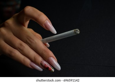 Beautiful hand with painted nails and a smoking cigarette on a black background.