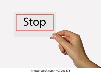 Beautiful hand of a young girl holding a card on a white background with the words Stop
