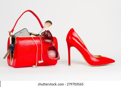 Beautiful handbag with women's accessories stands near the red shoes.