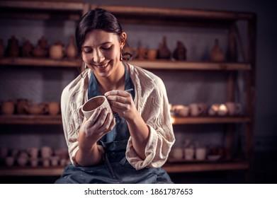 Schöner Handwerker, der eine Tonvase auf einem Töpferrad formt. Handarbeit.