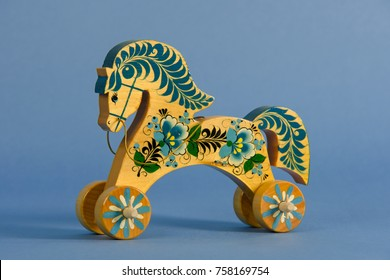 Beautiful handmade horse toy painted in traditional Russian hohloma style in studio against blue background.