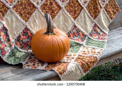 beautiful handmade quilt with fall colors, is paired with a small orange pumpkin on a sunny wood bench
