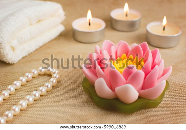 Beautiful handmade soap shaped like lotus flower. Burning candles, string of pearls and towel on the background. Spa concept.