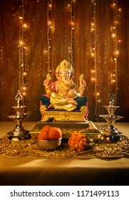 Beautiful handmade statue of Ganesha. Ganapati Festival set up and decoration with traditional lamps, prasad and lighting. 'Ganeshostav' is celebrated in almost every home in Maharashtra, India.