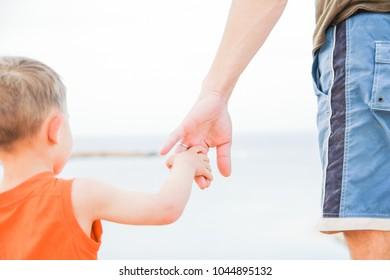 Beautiful hands of parent and child on sea background