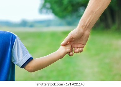 beautiful hands of parent and child outdoors in the park