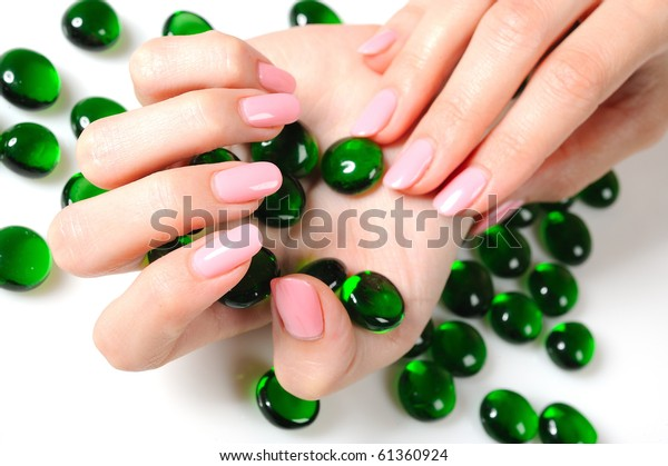Beautiful hands with perfect nail pink manicure and green decorative stones. isolated on white background