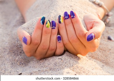 Beautiful hands with a professional manicure on the sand. Bright and beautiful manicure. Macro shooting hand. Photo for fashion magazines, websites and backgrounds.