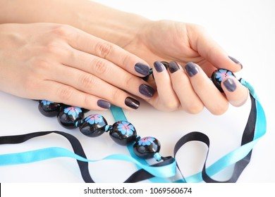 Beautiful hands of a young woman with dark manicure holding black necklace