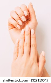 Beautiful hands of young woman with manicure, nails of beige pastel color with art design. Concept of beauty salon.