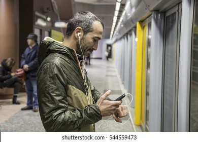 beautiful handsome Young stylish man with headphones on metro underground waiting