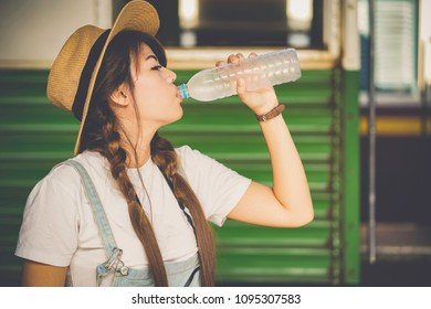 beautiful happiness asian woman drinking of water traveler adventure outdoor at train station,Travel and lifestyle concept.