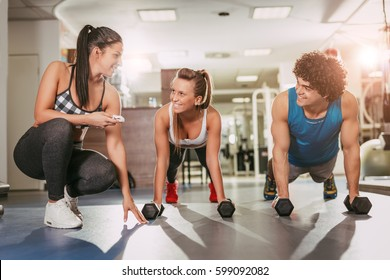Beautiful happiness couple exercising at the gym with a female personal trainer.