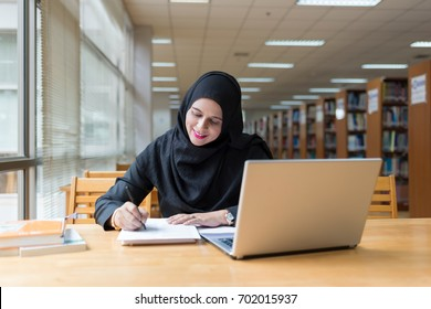 Beautiful happiness muslim girl writing notebook in library.