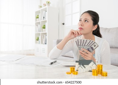 beautiful happiness woman holding cash thinking buying new house and sitting in living room counting saving money hoping dreaming come true.