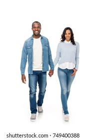 beautiful happy african american couple holding hands and walking together isolated on white