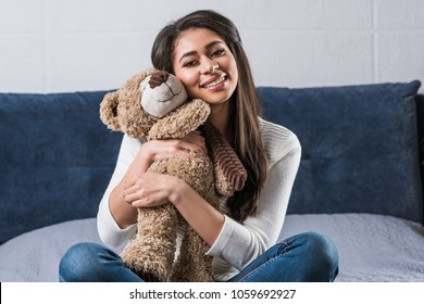 beautiful happy african american girl hugging teddy bear and smiling at camera on bed