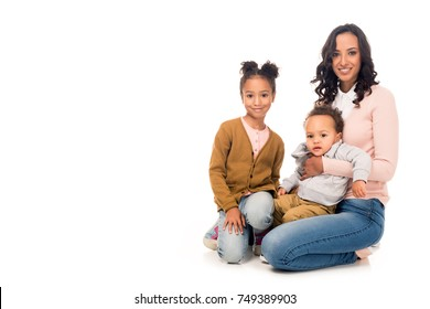 beautiful happy african american mother with adorable little kids smiling at camera isolated on white
