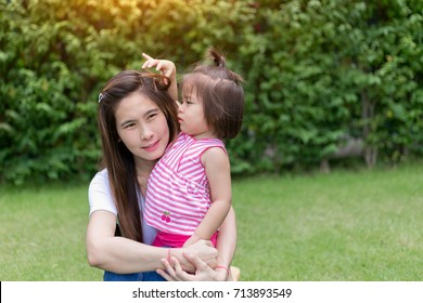 beautiful happy asian mother and daughter  sitting on the lawn.