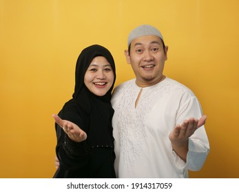 Beautiful happy Asian muslim couple wearing casual clothes smiling friendly offering handshake as greeting and welcoming