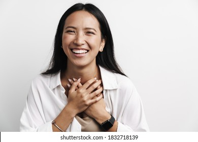Beautiful happy asian woman laughing while posing with hands her chest isolated over white background