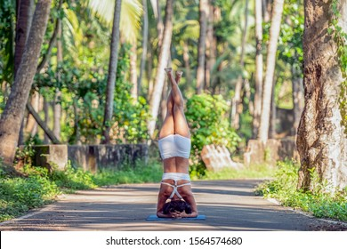 Beautiful and happy asian woman practices yoga in the jungle between palms tree at sunrise (sunset) healthy life in island of Bali, Indonesia ( india, goa) Meditation, calmness and relax