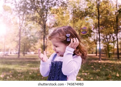 beautiful happy baby girl having fun in autumn park. Cute little girl is playing outdoor. girl playing in the sun