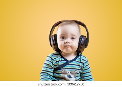 beautiful happy baby with headphones listening to music
