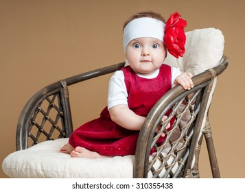 Beautiful happy baby in a red dress. Baby girl.