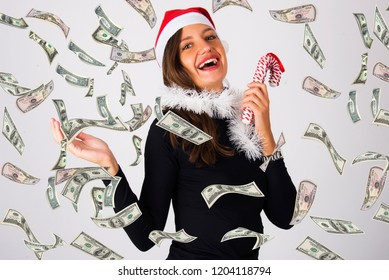 beautiful happy blond girl with money falling down with santa red hat new year concept