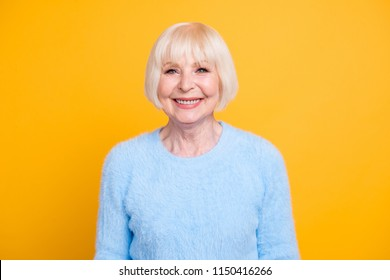 Beautiful and happy blond hair grandma looking at camera isolated on yellow background
