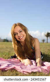 Beautiful happy blonde woman lying on a grass outdoor and smiling