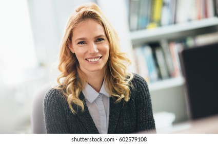Beautiful happy blonde woman in office smiling