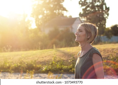 Beautiful happy blonde woman smiling and enjoying her time outside in park
