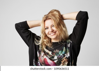 Beautiful happy blonde women touching her hair hands and smiling, on gray background. Studio shot.
