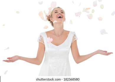 Beautiful happy bride being showered with petals over white background