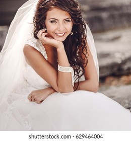 beautiful happy bride between columns in ancient place, wearing wedding dress and long veil