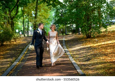 beautiful and happy bride and groom walking in the park