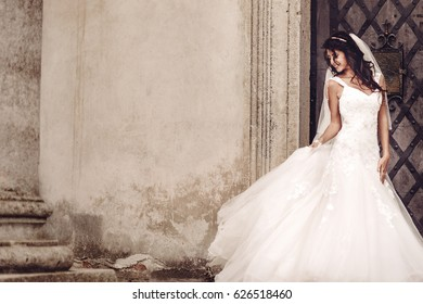 beautiful happy bride next ancient castle door, wearing wedding dress and long veil