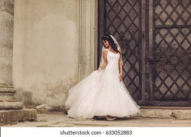 beautiful happy bride next ancient castle door, wearing wedding dress and long veil