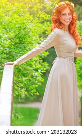 Beautiful happy bride wearing long beige dress and flower wreath in red hair, standing on little bridge in fresh summer park, happiness and love concept