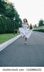 beautiful happy bride in wedding dress running on road